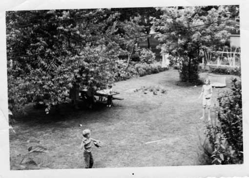 One of the Big Kids (me) condescends to 'play' with Roger. That's Laura lurking by the picnic table. And that's Doug's playpen. (Remember those?)
